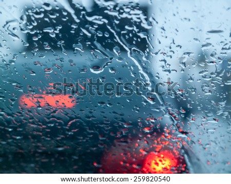 Rainy street traffic lights, view through wet glass. Abstract  background. - stock photo