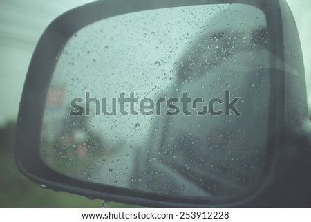 Rainy view in car side mirror with drops and lights.