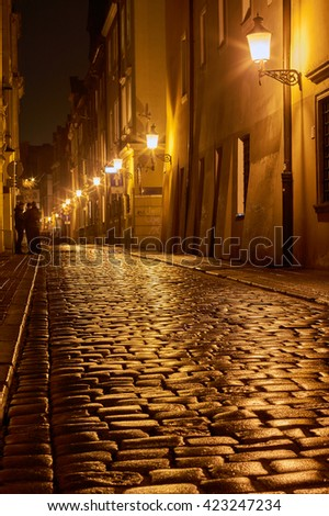 Rainy walk the cobbled street at night in Poznan