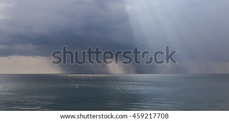 Rainy weather over the sea. Shower and rays of the sun on the horizon of the sea created a fantastic panorama. - stock photo