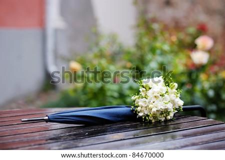 Rainy wedding: bridal flowers and umbrella on wet table - stock photo