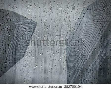Rainy window with skyscraper background - stock photo