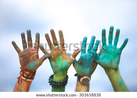 Raised colorful hands at holi festival - stock photo