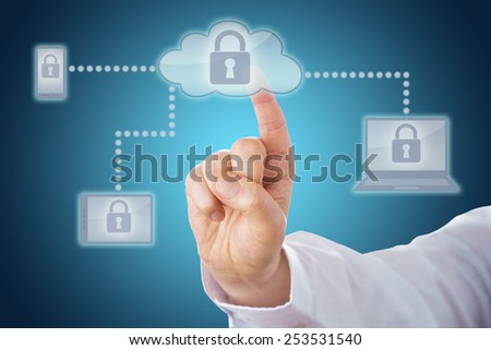 Raised index finger touching a locked cloud icon linked via dotted lines to mobile and tablet devices within a network. Cell phone, tablet and laptop computer all display the lock on-screen. Close up. - stock photo