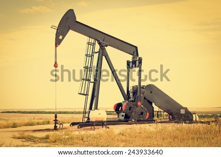 Raised pump jack in south central Colorado, USA, ready to start the down stroke to load the lifting pump with crude oil. Retro instagram look.
