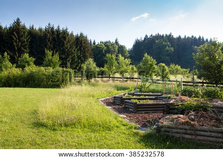raised vegetable beds in the rural natural garden with orchard and blooming flowers - stock photo