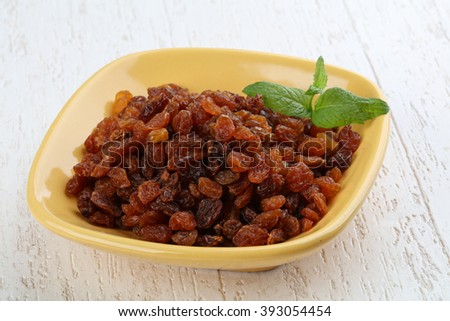 Raisin in the bowl on the wood background