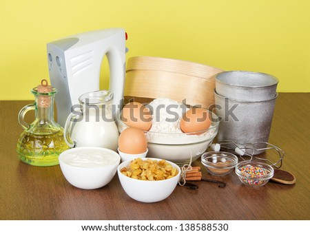 Raisin, spices, means for ornament and a form for Easter, on a a table, on a yellow background