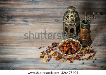 Raisins and dates on wooden background. Arabic till life with vintage oriental lantern and mill. Food concept. Retro toned picture - stock photo