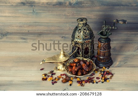 Raisins and dates on wooden background. Vintage oriental lantern and mill. Retro style toned picture - stock photo