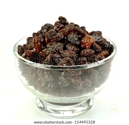 Raisins in a glass bowl on a white background.