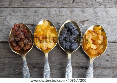 Raisins in metal spoons on wooden table - stock photo