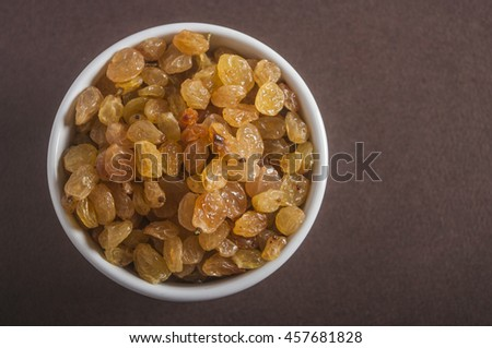 Raisins in saucer on wooden table, closeup