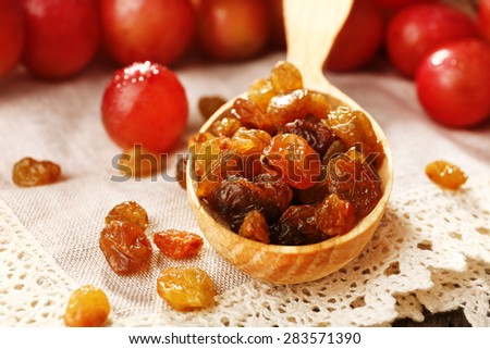 Raisins in wooden spoon with grapes on table close up - stock photo