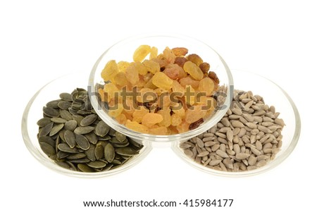 Raisins ,pumpkin seeds,sunflower seeds in a glass bowl. Isolated on white.