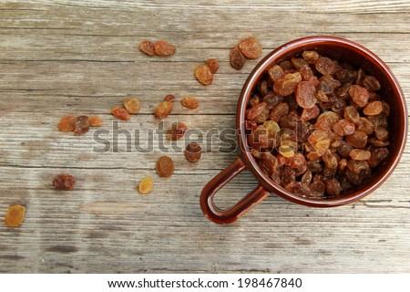 Raisins Raisins in the bowl on the wooden table - stock photo