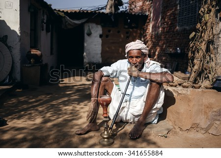 RAJASTHAN, INDIA - JANUARY 9, 2015: Old Indian man smoking hookah on January 9, 2015 in Rajasthan, India - stock photo