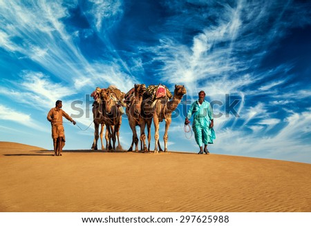 Rajasthan travel background - two Indian cameleers (camel drivers) with camels in dunes of Thar desert. Jaisalmer, Rajasthan, India - stock photo