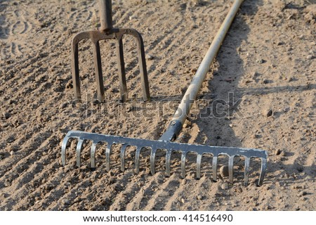 Rake and pitchfork on loosened soil closeup