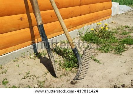 Rake and shovel on a garden site  - stock photo