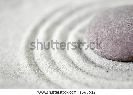 Raked sand around a pebble in a small tabletop rock garden (shallow DOF) - stock photo