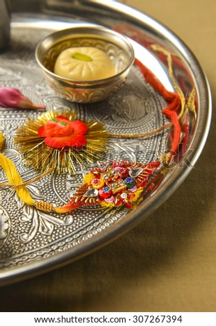 Raksha Bandhan. Traditional Rakhis placed in a decorative plate with sweet. - stock photo