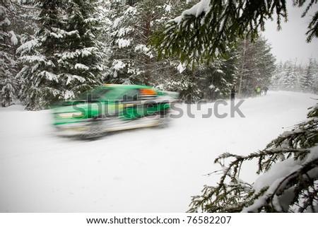 Rally Car blasting through a snowy road - stock photo
