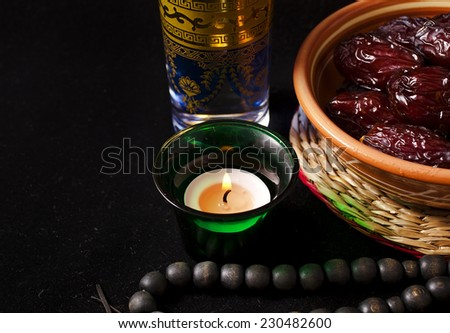 Ramadan dates with a glass of water, still life on a black background  - stock photo