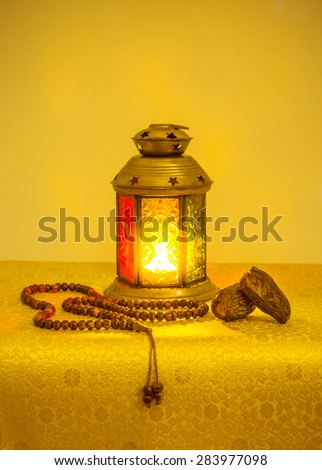 Ramadan festive background. Traditional ramadan lamp with date fruit and islamic prayer beads. Bright golden yellow color scheme.  - stock photo