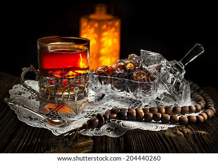 Ramadan lamp and dates still life on black background - stock photo