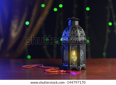 Ramadan  lamp and rosary against xmas lights decoration - stock photo