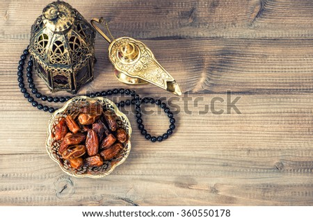 Ramadan lamp, rosary and dates on wooden background. Holidays decoration - stock photo