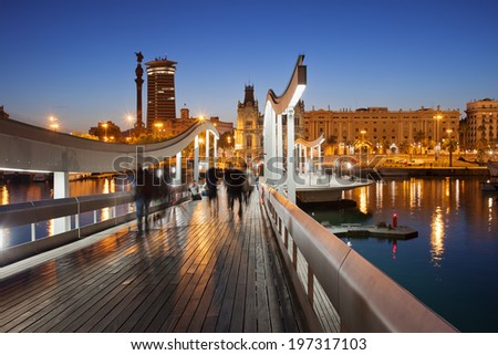 Rambla de Mar wooden walkway over Port Vell in the city of Barcelona at night in Catalonia, Spain.
