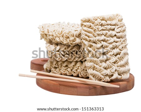 Ramen instant raw noodles on wooden plank 3/4 with chopsticks general view