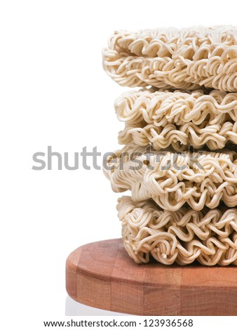 Ramen instant raw noodles staked on wooden plank side border - stock photo