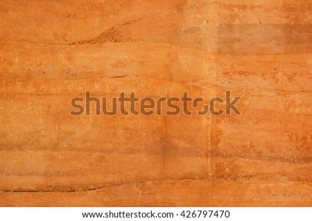 Rammed earth wall texture with different shades of orange soil