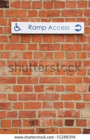 ramp access sign on a brick wall background - stock photo