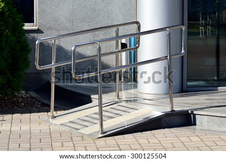 Ramp for wheelchair entry with metal handrails - stock photo