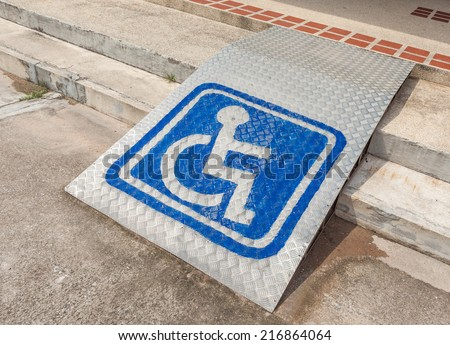 Ramped access, using wheelchair ramp with information sign on floor background for disabled people. - stock photo