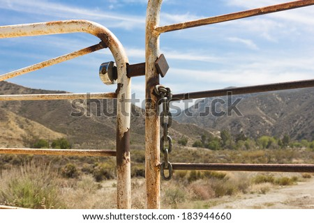 Ranch gate is locked and chained with mountains and brush in the background. - stock photo