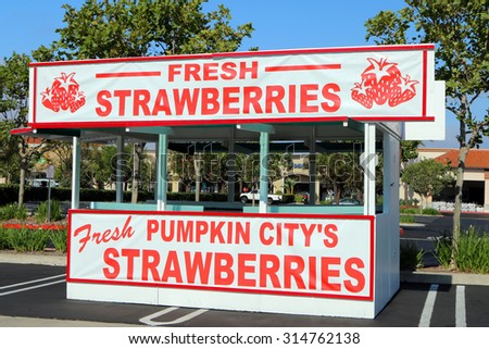 RANCHO SANTA MARGARITA, CA- CIRCA AUGUST, 2015:  Roadside strawberry stand in the middle of a parking lot of a busy suburban shopping center.