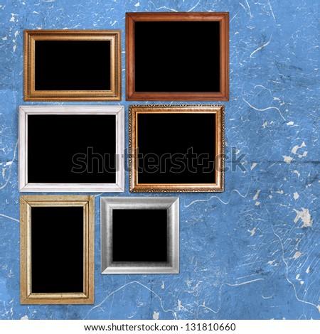 Random vintage frames in blue grunge room - stock photo