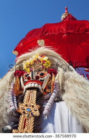 Rangda Mask under red umbrella in temple - traditional spirit of Bali at ceremony Melasti before Balinese New Year and silence day Nyepi Holidays, festivals, rituals, art, culture of Indonesian people - stock photo