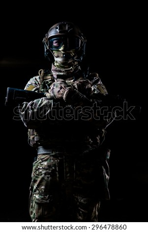 Ranger in camouflage,mask and helmet  standing with rifle and looking at  camera on black background/Ranger in camouflage,mask and helmet standing with rifle and looking at  camera on black background - stock photo