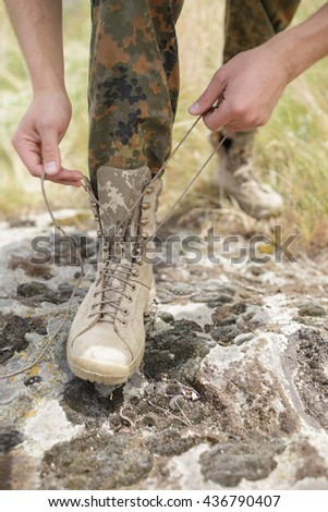 Rangers boots and hands tying bootlaces on stone