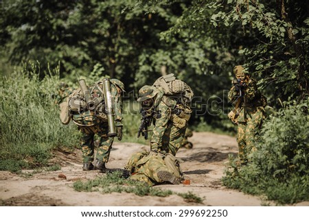 rangers team evacuate wounded comrade from the battlefield - stock photo