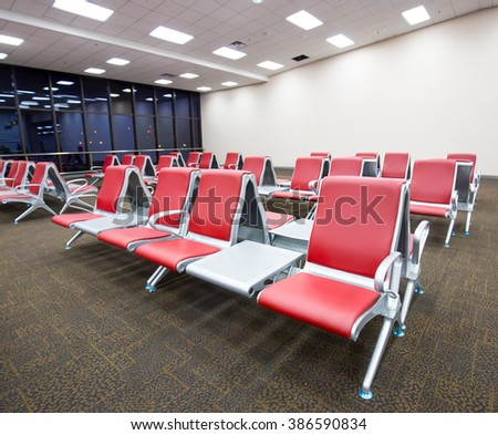 Ranges of empty red chairs in airport use for waiting to go to airplane