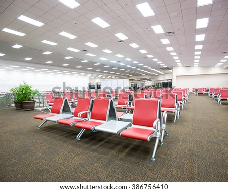 Ranges of empty red chairs in airport use for waiting to go to airplane - stock photo