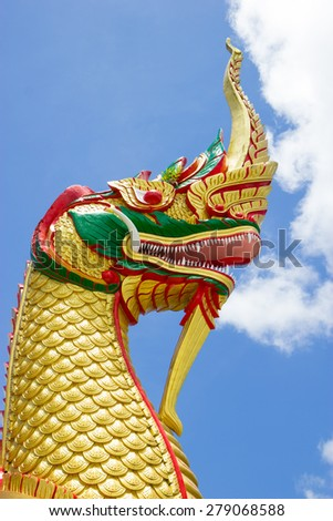 RANONG , THAILAND : The golden serpent head of naga statue on blue sky background - stock photo