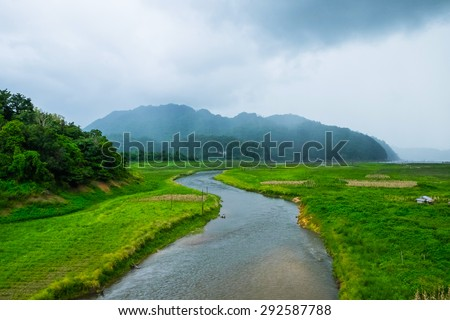 Rantee curve river with mountain cloudy fog in cultivated area